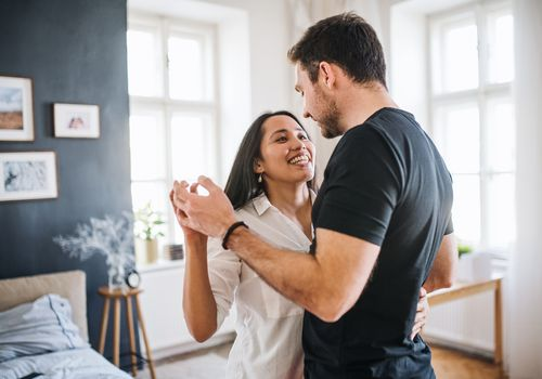 Photo of a happy young couple dancing in their bedroom