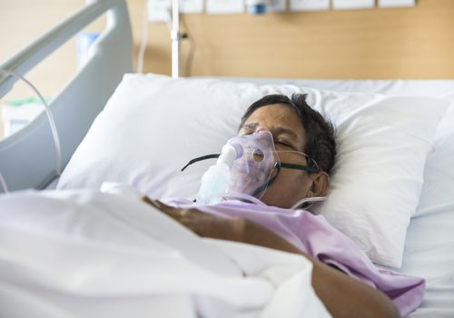 Old woman with a ventilator mask in hospital