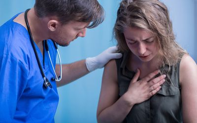 Woman with doctor having trouble breathing
