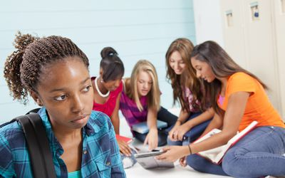 Girl standing alone in front of group of girls