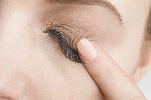 woman with false eyelashes poking her closed eyelid