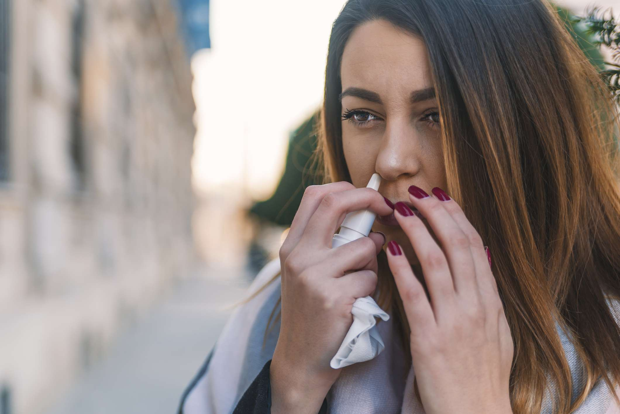 Woman standing outside using a nasal spray