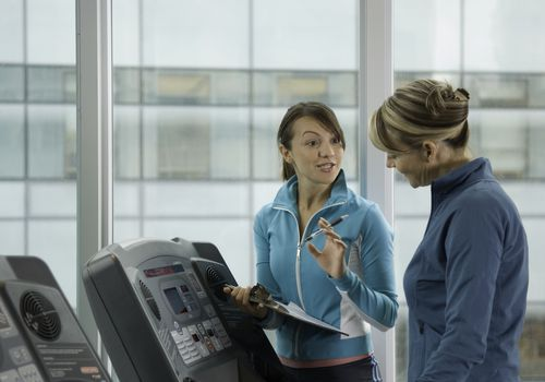 Photo of a woman PT speaking with a patient on a treadmill.