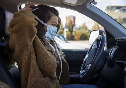 Woman putting on face mask while she's in the car.