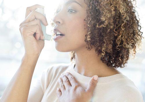 A woman using an inhaler.