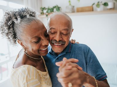 Carefree senior couple dancing in the living room - stock photo