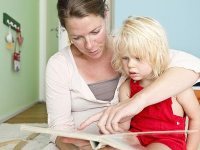 Mom reads and points to a picture in a book