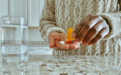 Woman pouring pills into hand.