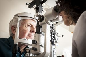 Older man during eye exam with female eye doctor.
