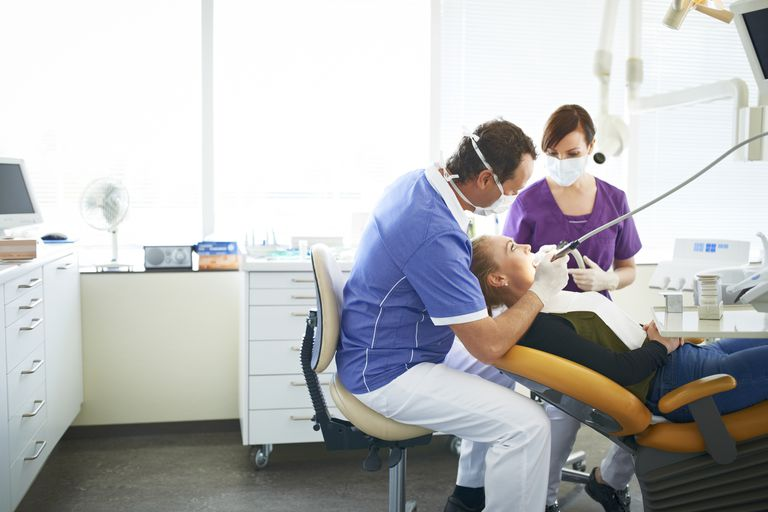 A dentist and his assistant work on a patient