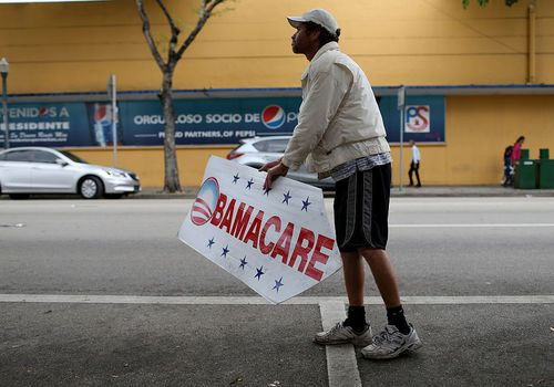 Man holding a sign advertising Obamacare