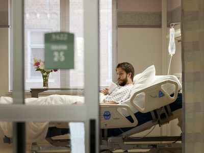 A man sitting and waiting in his hospital bed