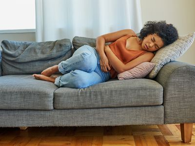 A young woman experiencing stomach pain while lying on a sofa at home.