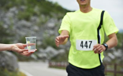 Italy, Trentino, man receiving cup of water during a running competition near Lake Garda