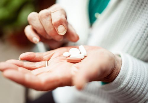 Older adult holding pills in her hand.