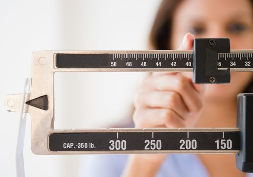 woman weighing herself while on Depo Provera