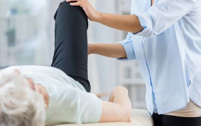 Senior woman and therapist work on her knee