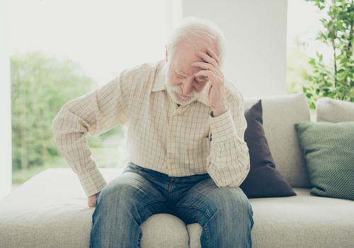 Older man sitting down due to dizziness