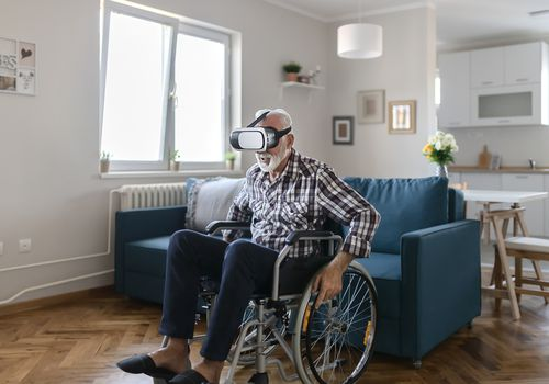 Older man in a wheelchair uses a virtual reality headset.