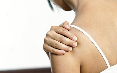 Image of a woman holding her shoulder.