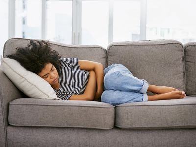 Woman laying on the couch in pain from endometriosis