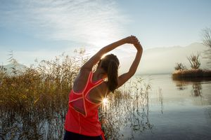 woman stretching lower back in front of a lake