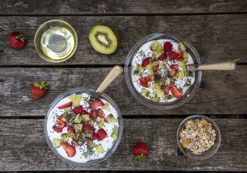 Strawberry kiwi yogurt with cereals, chia seeds, agave syrup in glass bowl on wood