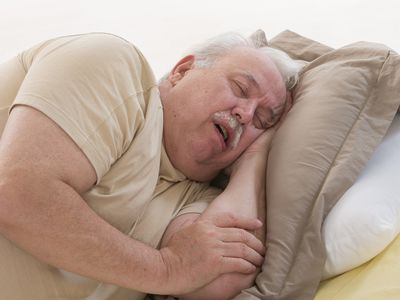 Man snoring while napping on couch