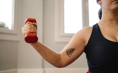 front view of the arm of a young athlete woman with a dumbbell