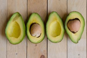 Four halves of avocados on wood table