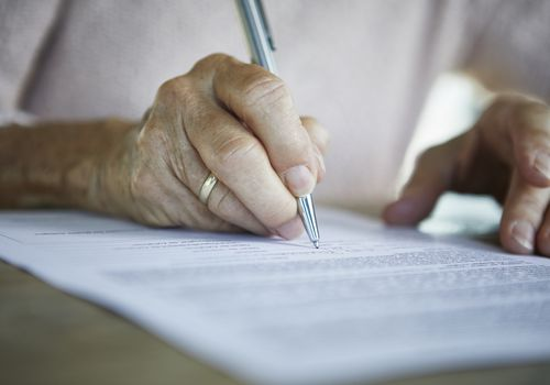 Close up of an older person's hands holding a silver pen and signing a document.