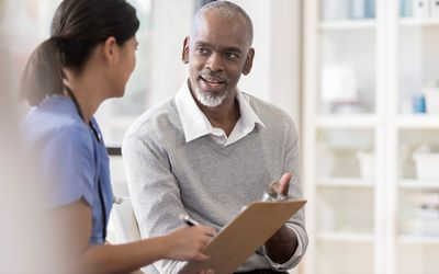Senior man discusses diagnosis with doctor