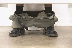 Close up of pants around businessman's ankles in restroom