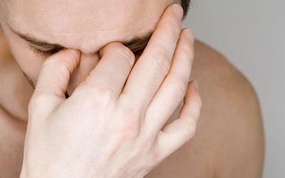 Man holding bridge of nose.