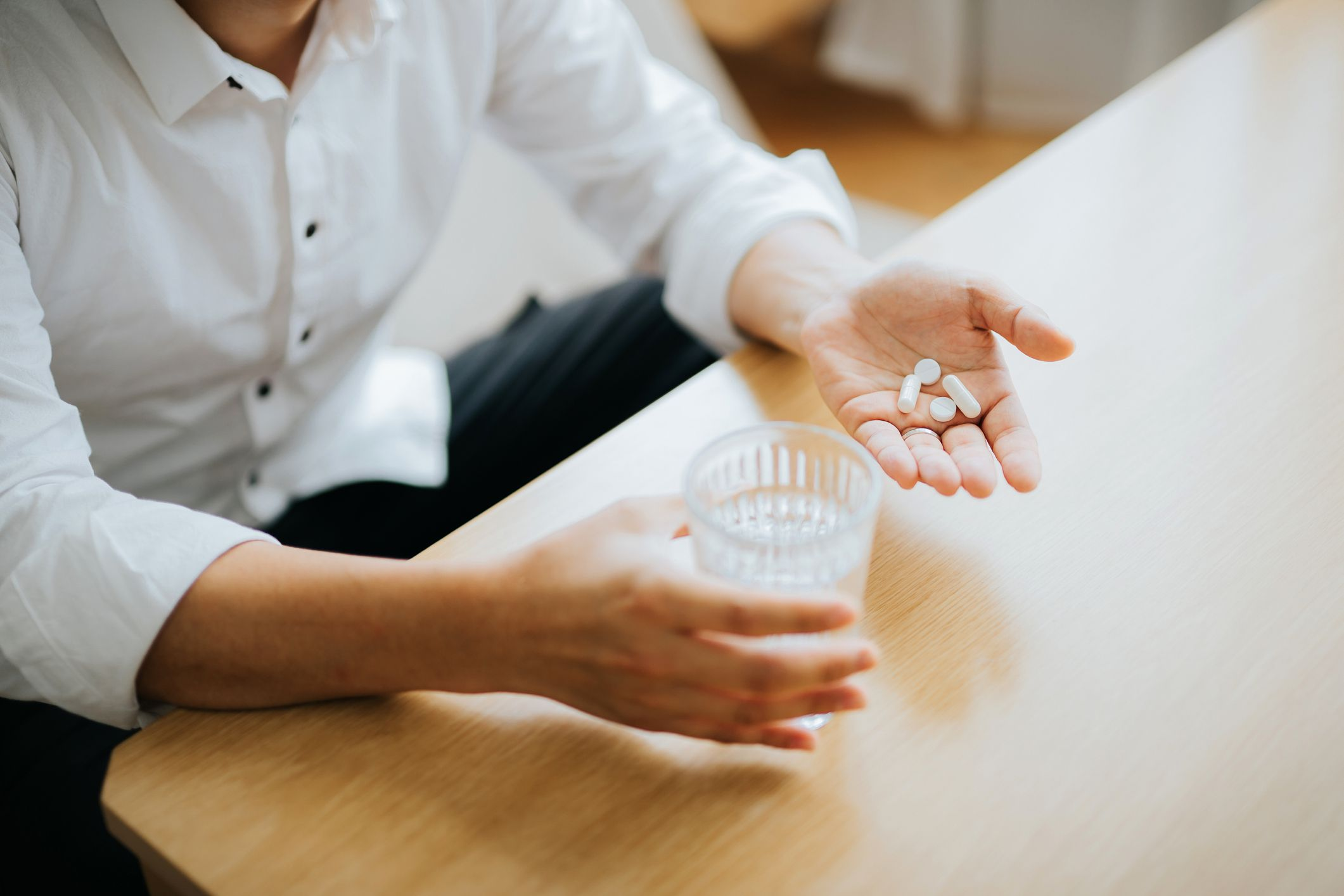 Close up of man holding a glass of water and medication in his hand