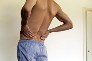 Back and knee pain. Man experiencing lower back pain, croppeds