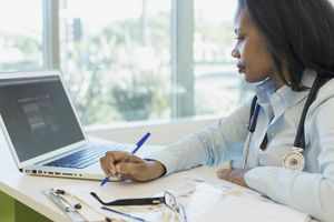 Female doctor looking at laptop screen while preparing report at desk in clinic