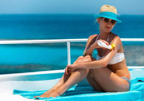 Woman applying suntan lotion on a boat.