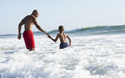 Father and son playing in surf