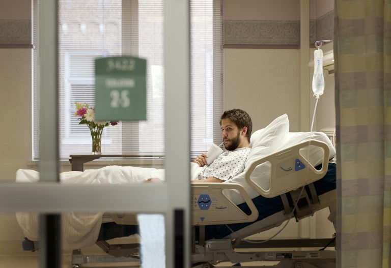 man drinking from cup in a hospital bed