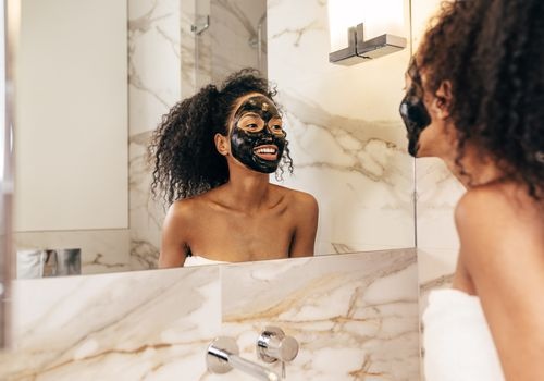 Happy Woman With Face Mask In Bathroom