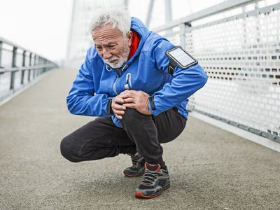Senior man having knee injury after running