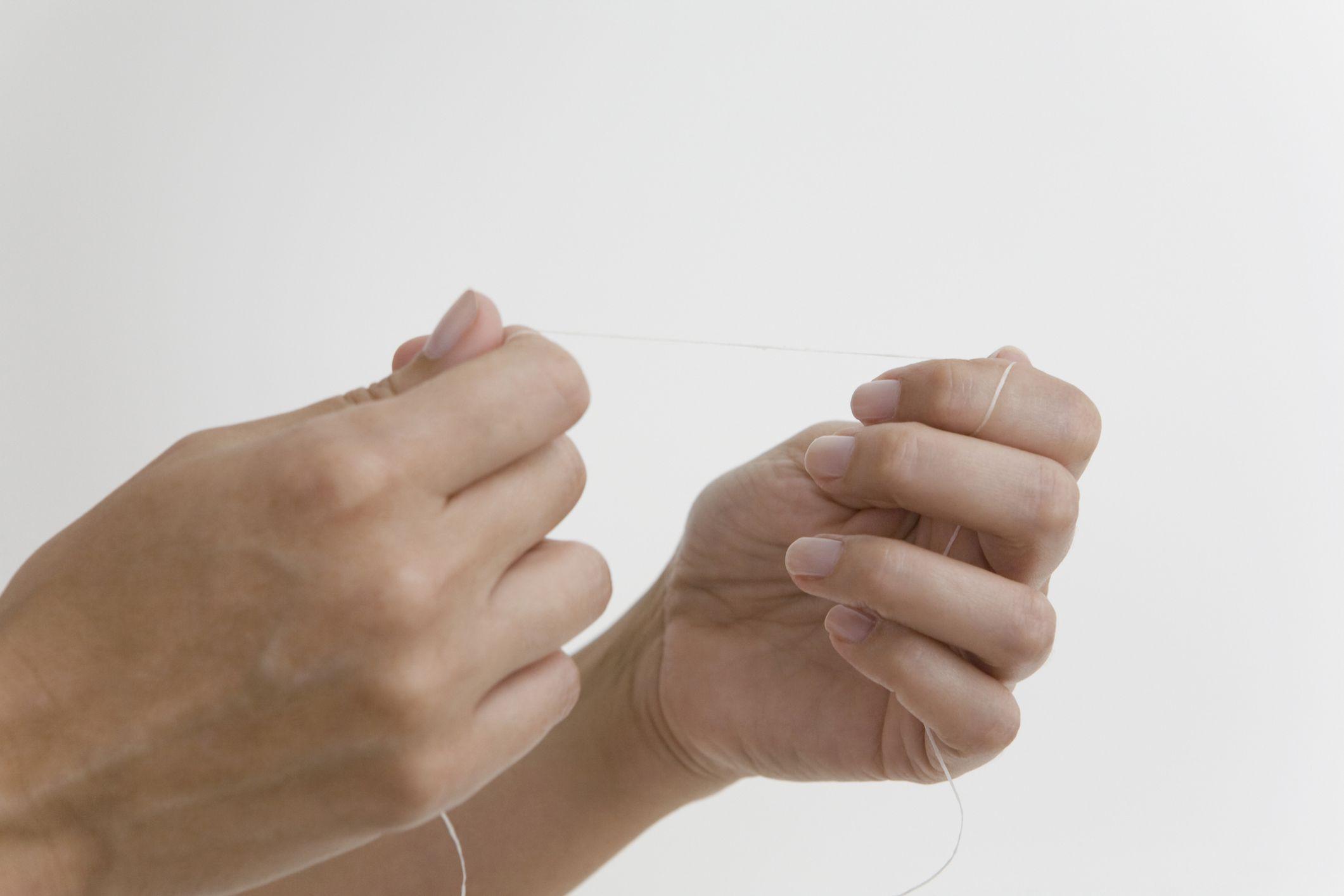 woman's hands holding dental floss