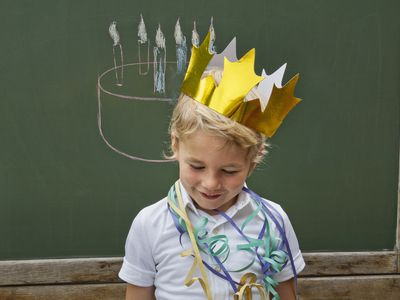 a young child wearing a paper crown