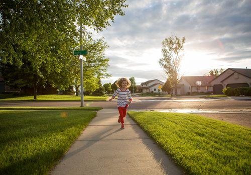Little Girl Running down a sidewalk in a neighborhood