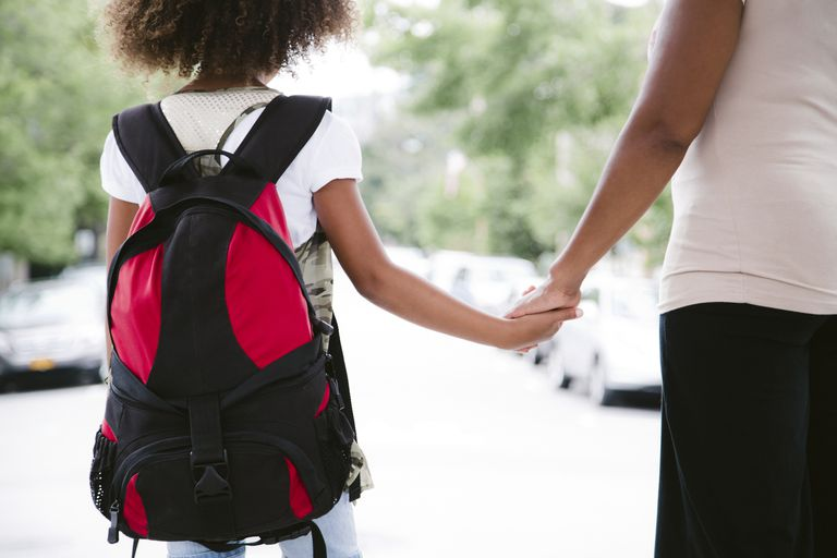 A school child wears a back pack.