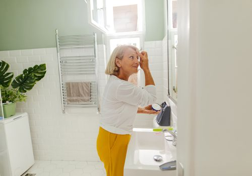 Senior woman doing her morning routine in bathroom