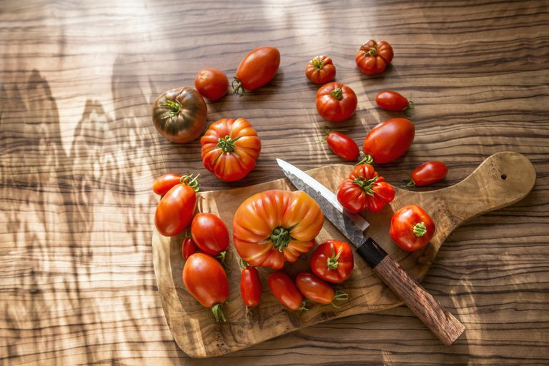 Directly above shot of variety of tomatoes with knife on cutting board, Munich, Bavaria, Germany
