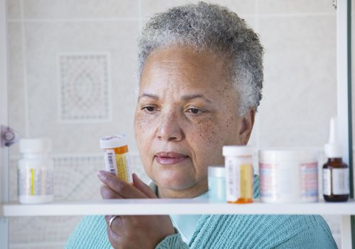 A woman examining her prescription bottles