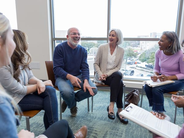 The multi-ethnic therapy group meeting for grief recovery has a lighthearted moment.